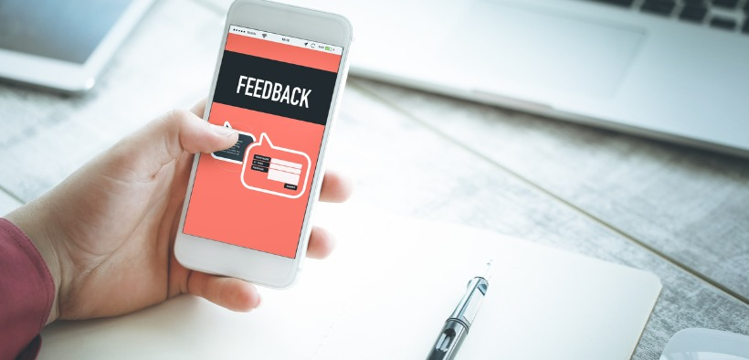 """A hand holding a smartphone with the word """"feedback"""" on the screen."""