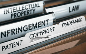 "Image of a folder with tabs reading ""patent,"" ""copyright,"" ""trademark,"" ""infringement,"" ""law,"" and ""intellectual property."""