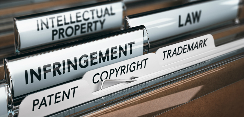 """Image of a folder with tabs reading """"patent,"""" """"copyright,"""" """"trademark,"""" """"infringement,"""" """"law,"""" and """"intellectual property."""""""