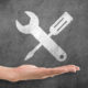 """A woman's hand positioned to """"catch"""" a drawing of screwdriver and a wrench."""