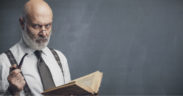A stereotypical old, bald, bearded white male professor stands scowling before a chalkboard, clutching a pipe and reading an old book